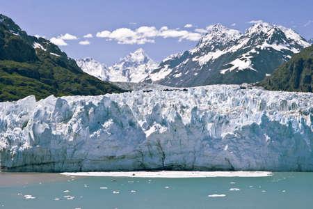 toward: Glacier sliding toward the ocean colors the water as it calves.