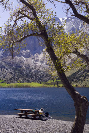 Man Fishing from picnic table at Convict Lake, CA.
