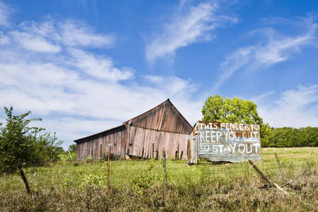Dilipidated barn sits behind a fence and a warning sign in Kansas Stock Photo - 2024932