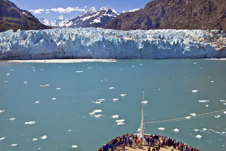 A crowd gathers at the bow of a cruise ship near a glacier