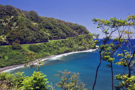 The Hana Highway clings to the coast in a tropical rain forest  Stock Photo