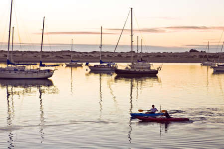 Two boys row canoes among larger boats at sunset in Morro Bay, California