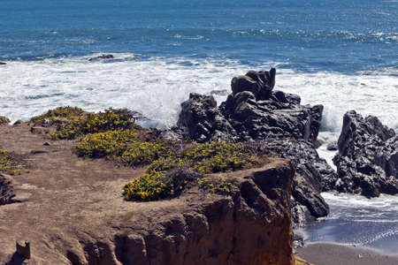 Waves pound the rugged rocky outcroppings along Moonstone Beach in Cambria, California. Stock Photo