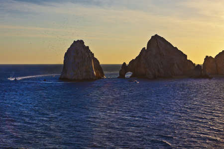 Famed rock formations in Cabo San Lucas, Mexico, against a setting sun
