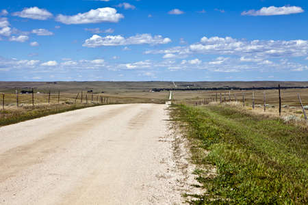 Gravel road takes a crooked path over rolling hills in eastern Colorado under scattered clouds Stock Photo - 10628033