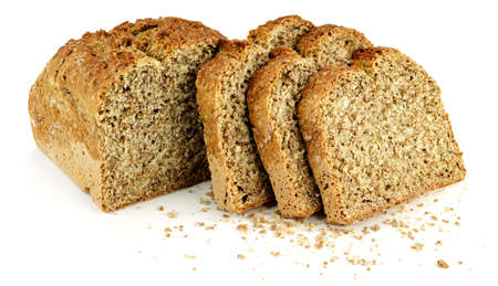 a loaf of bread with three slices and bread crumbs on a white table Stock Photo