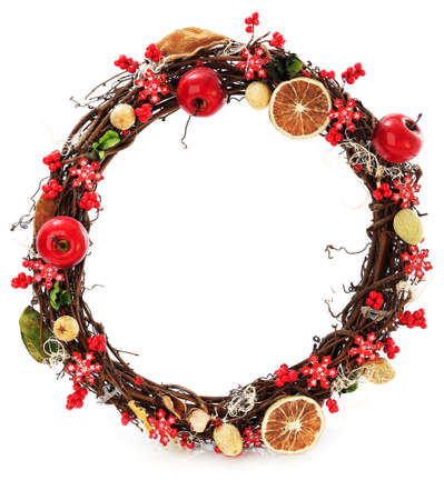 A seasonal wreath decorated with a dried oranges and floral details on a white background photo
