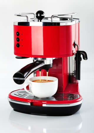 A red vintage looking espresso coffee machine is making a coffee on a white background