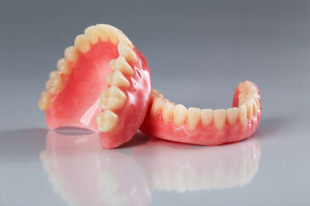 A set of dentures on a shiny gray background photo