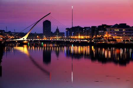Noordelijke oever van de rivier de Liffey in Dublin City Centre in de nacht met Samuel Beckett Bridge en The Spire gezien vanaf de zuidoever Stockfoto