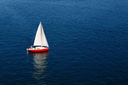 A lone voile blanche d'un voilier rouge sur une mer bleue calme Banque d'images