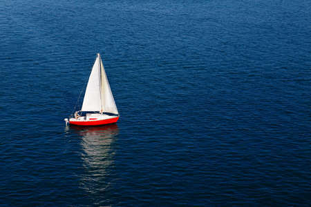 small boat: A lone white sail of a red sailboat on a calm blue sea