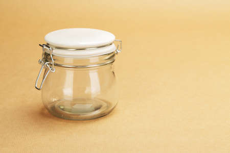 An empty jar with a closed white lid on a background of a wrapping paper photo