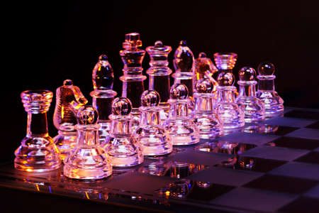 chessboard: Glass chess on a chessboard lit by a colorful blue and orange light and placed on a glass chessboard Stock Photo