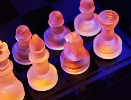 Glass chess on a chessboard lit by a colorful blue and orange light and placed on a glass chessboard Stock Photo