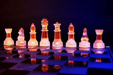 chess king: Glass chess on a chessboard lit by a colorful blue and orange light and placed on a glass chessboard Stock Photo