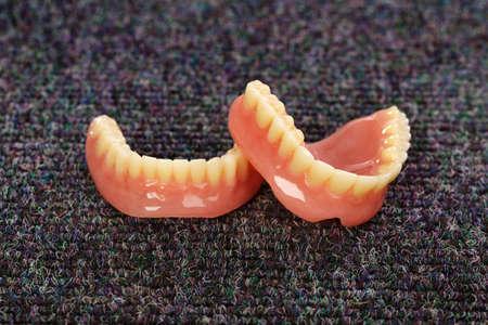 false teeth: A set of dentures laying on a dark gray carpet