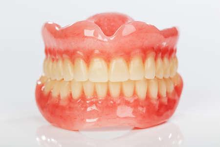 falso: Un conjunto de prótesis dentales sobre un fondo blanco brillante