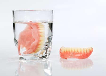 Een kunstgebit in een glas water op een witte backgrounda kunstgebit in een glas water op een witte achtergrond Stockfoto