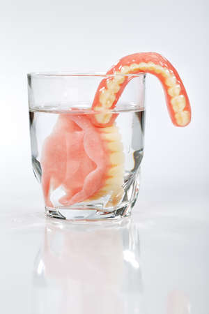 false teeth: A set of dentures in a glass of water on a white background Stock Photo