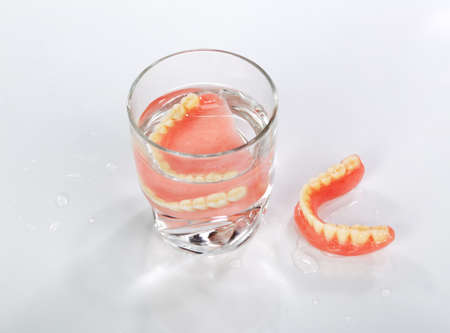 A set of dentures in a glass of water on a white background photo