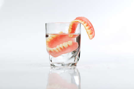 A set of dentures in a glass of water on a white background Stock Photo