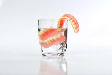 Een kunstgebit in een glas water op een witte achtergrond