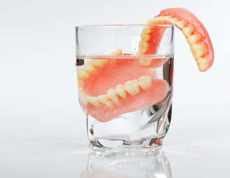 白い背景の上に水のガラスで入れ歯のセット