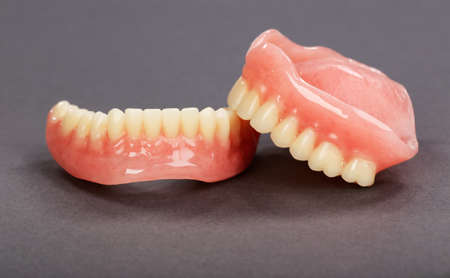 A set of dentures on a gray background