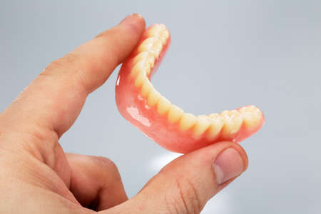 Hand holding a set of dentures on a gray background