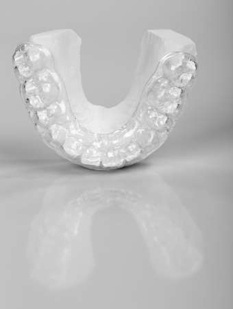Translucent upper essix retainer on a plaster study model placed on a gray background photo