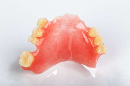 A partial denture on a shiny gray background