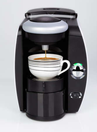 with coffee maker: A black modern espresso coffee machine is making a coffee on a white background