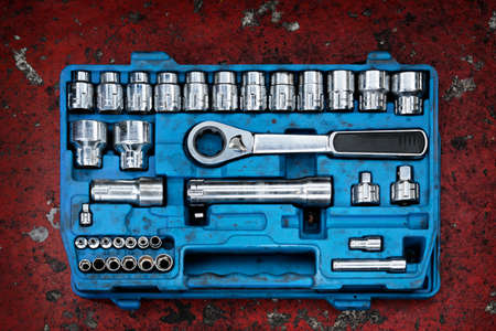 Tools in a blue toolbox on a red background photo