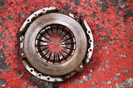 scrap iron: an old worn out vehicle clutch on a red background