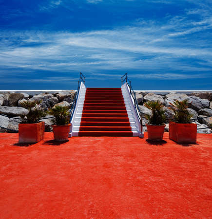 Red carpet stairway leading to heaven with stanchions barriers on both sides photo