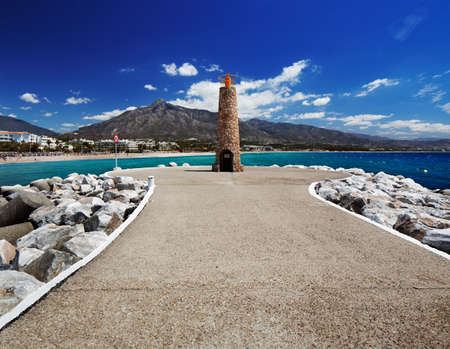 Lighthouse at the end of breakwater in the Puerto Banus in Marbella, Spain  Marbella is a popular holiday destination located on the Costa del Sol in the southern Andalusia