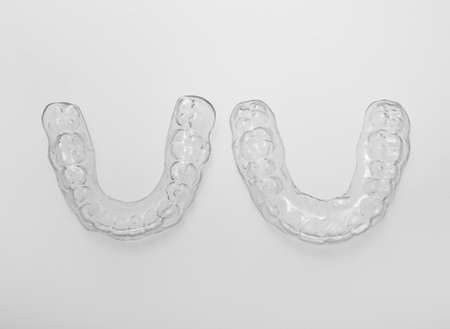 Translucent upper and lower essix retainers on a gray background photo