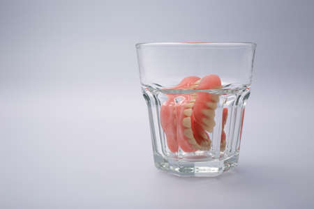dental resin: A set of dentures in a glass of water on a white background Stock Photo