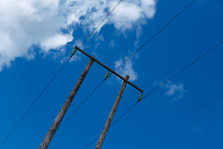 isolator insulator: Old wooden electric post against blue sky and beautiful clouds