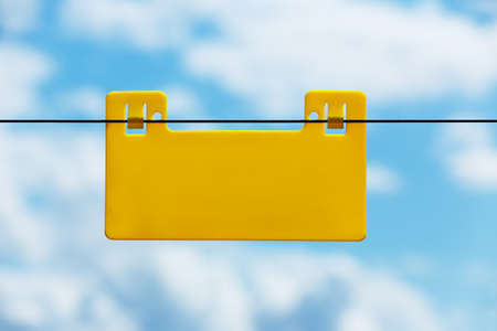 fence panel: Blank yellow info plate hung on an electrical fence against blue sky with clouds Stock Photo