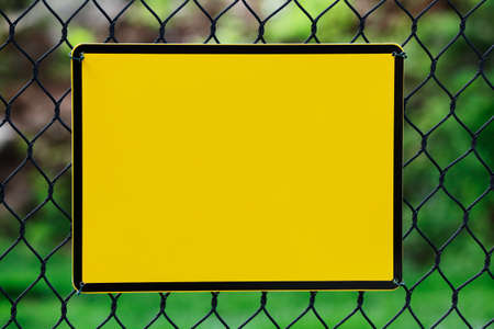 Blank yellow info plate hung on a wire fence photo