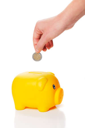 Yellow piggy bank is getting two euro coin from a hand on white background photo