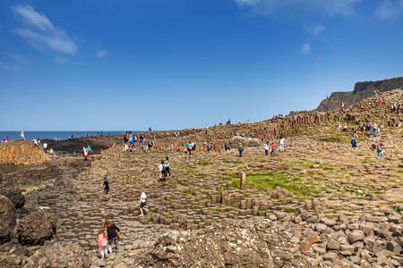 Thousands of tourists visiting Giants Causeway in County Antrim of Northern Ireland, containing about 40000 interlocking basalt columns from ancient volcanic eruption