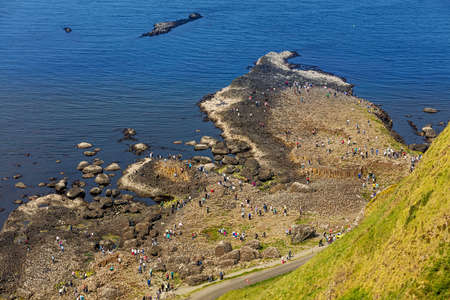 Thousands of tourists visiting Giants Causeway in County Antrim of Northern Ireland, a World Heritage Site by UNESCO containing about 40000 interlocking basalt columns from ancient volcanic eruption