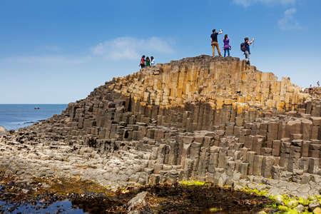 北アイルランドのアントリムにある巨大なコーズウェイを訪れる何千人もの観光客が、ユネスコの世界遺産に登録されていて、古代の火山噴火によ