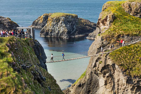 Thousands of tourists visiting Carrick-a-Rede Rope Bridge in County Antrim of Northern Ireland, hanging 30m above rocks and spanning 20m, linking mainland with the tiny island of Carrickarede