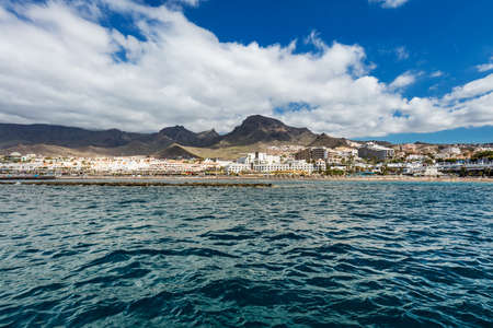 Vibrant scenery and deep-blue waters of the Tenerife west coastline as seen from a yacht. The dormant Teide volcano can be seen in the background. Many tourism resorts overlook the coastline. Stock fotó