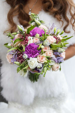 arm bouquet: Bouquet of roses and freesia in the hands of the bride. Bride with long hair dressed in a fur coat
