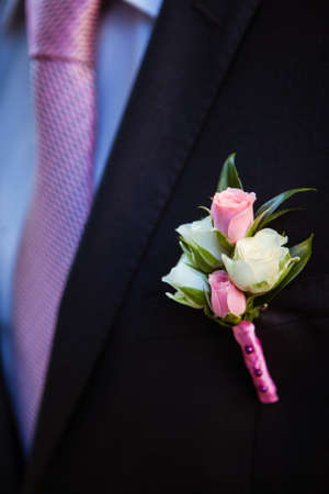boutonniere of pink and white rosebuds on the lapel of his jacket the groom's black Banque d'images